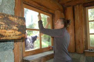 Volunteers Rachel Dentel and Nathan Adams work together to install a window.